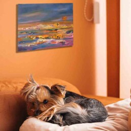 Photo of cute puppy sleeping in bed on a pillow, having the painting on the wall in the background, predominantly orange in the painting and its surroundings